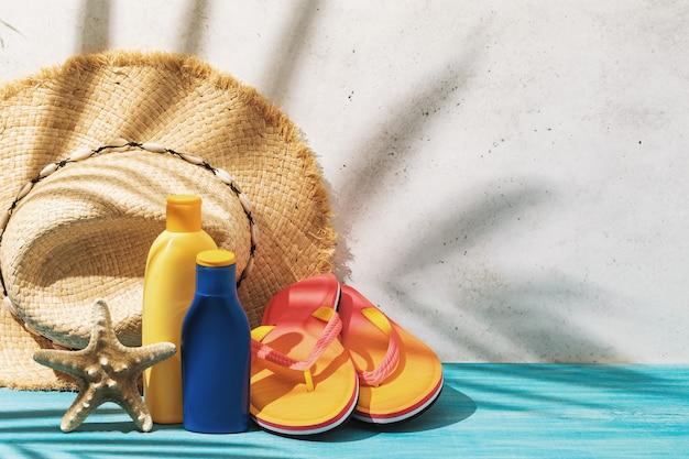 Chapéu de palha, protetor solar, chinelos de praia e estrela do mar na mesa de fundo de verão