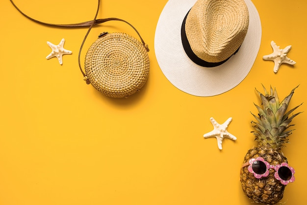 Chapéu de palha, saco de bambu, abacaxi em óculos de sol e estrelas do mar, vista superior