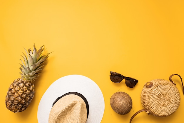 Chapéu de palha, saco de bambu, óculos de sol, coco, abacaxi sobre fundo amarelo, vista superior.