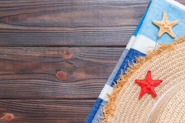 Chapéu de palha, toalha azul e estrela do mar em uma mesa de madeira escura. conceito de férias de verão vista superior com espaço de cópia