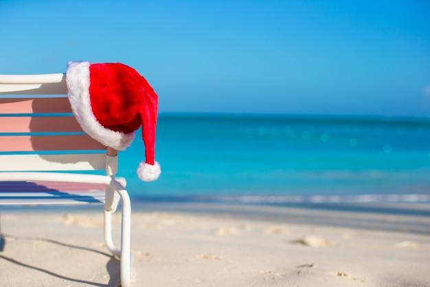 Chapéu de papai noel closeup na cadeira longue na praia tropical