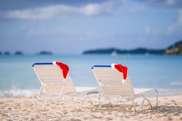 Chapéu de papai noel closeup na cadeira na praia branca tropical