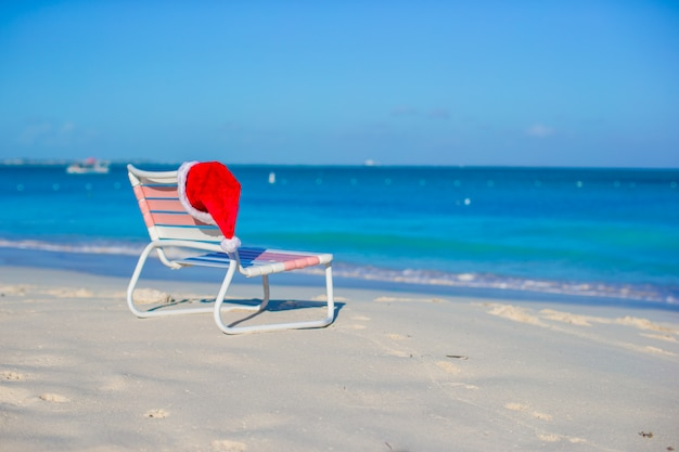 Chapéu de papai noel closeup na espreguiçadeira na praia tropical