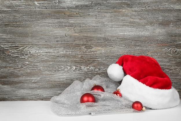 Chapéu de papai noel com decoração de natal em fundo de madeira
