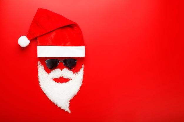 Chapéu de papai noel e barba feita de neve com óculos escuros