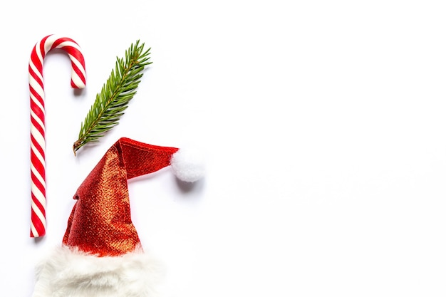Chapéu de papai noel e bastão de doces e galho de árvore do abeto no fundo branco ano novo criativo plano deitado com policial ...