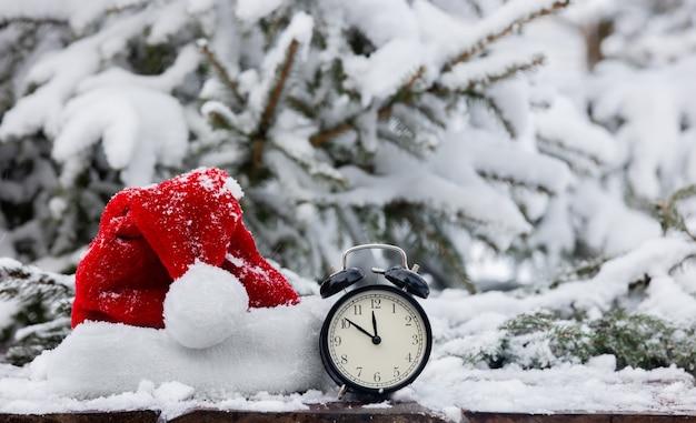 Chapéu de papai noel e despertador vintage em mesa de madeira durante nevasca