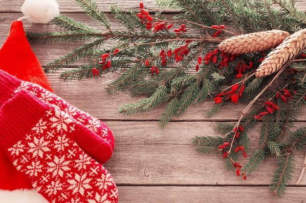 Chapéu de papai noel e luva vermelha em fundo de madeira velha