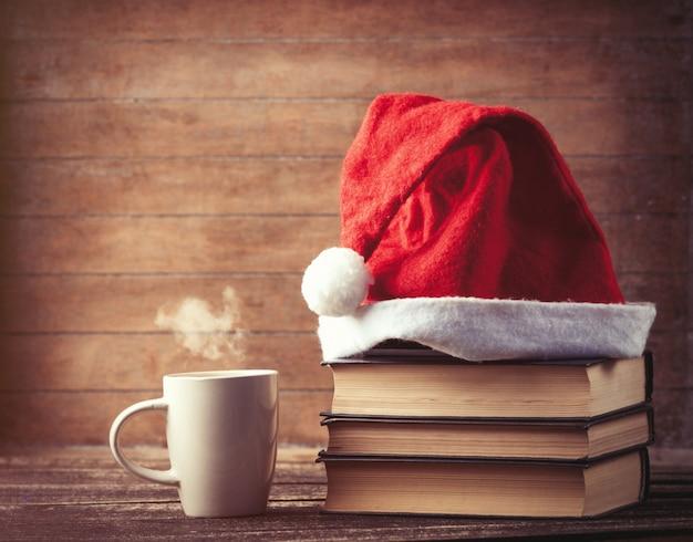 Chapéu de papai noel sobre livros perto de xícara de café ou chá quente