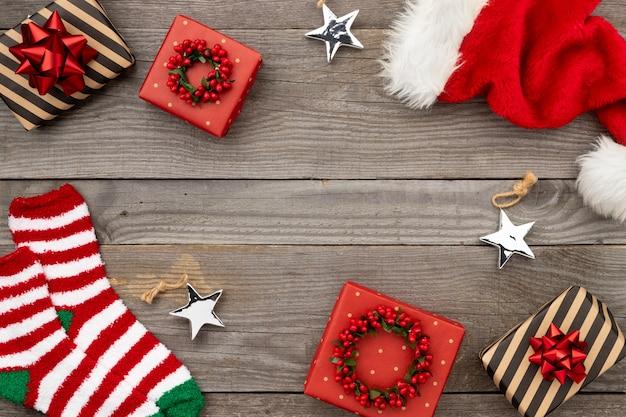 Chapéu de papai noel vermelho, caixas de presente e meias em madeira velha. plano de natal