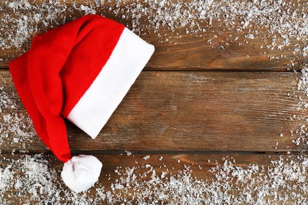 Chapéu de papai noel vermelho com flocos de neve em fundo de madeira
