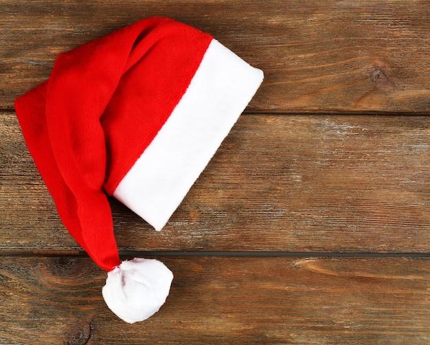 Chapéu de papai noel vermelho em fundo de madeira