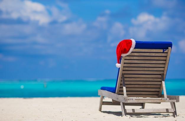 Chapéu de papai noel vermelho na cadeira longue na praia tropical branca
