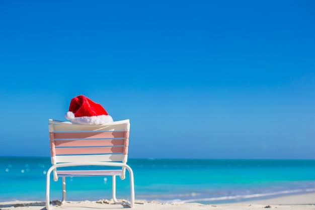 Chapéu de papai noel vermelho na espreguiçadeira na costa do mar