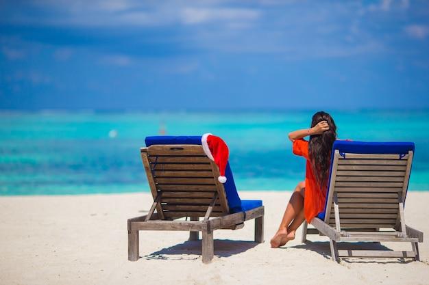 Chapéu de papai noel vermelho na espreguiçadeira na praia branca tropical