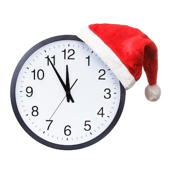 Chapéu de papai noel vermelho pendurado no relógio de parede redondo isolado no fundo branco. conceito de época de natal.
