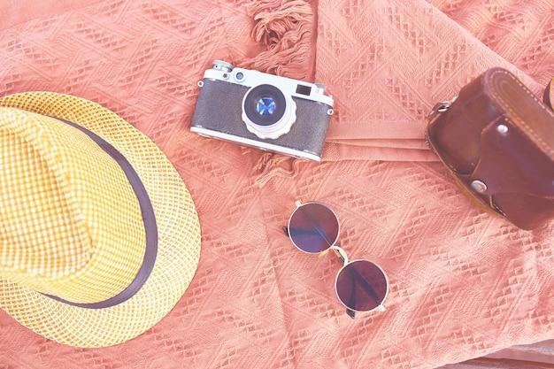 Chapéu de praia, câmera, óculos de sol na praia em um dia ensolarado. conceito de férias