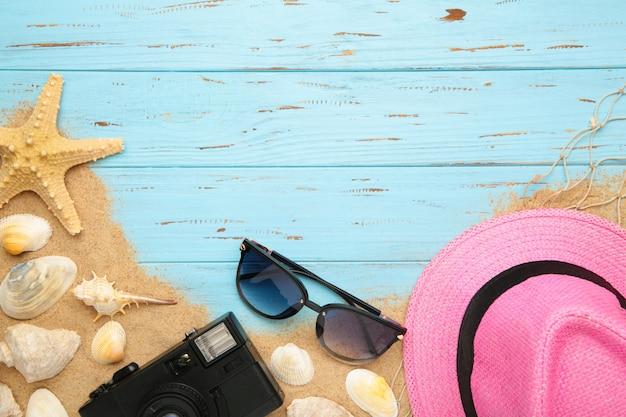 Chapéu de praia com conchas e areia no fundo azul