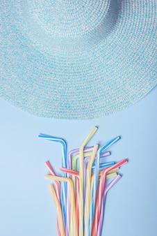 Chapéu de praia e coquetel em fundo azul