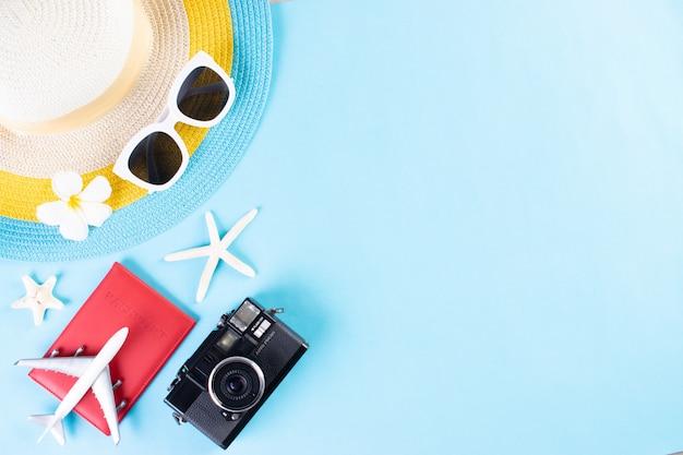 Chapéu de praia, óculos de sol, câmera, passaporte e flip flop sobre fundo azul claro. verão ou férias.