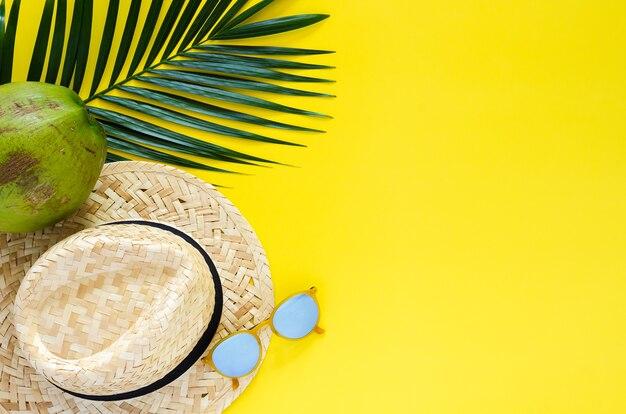 Chapéu de praia, óculos escuros e coco e folhas no fundo amarelo