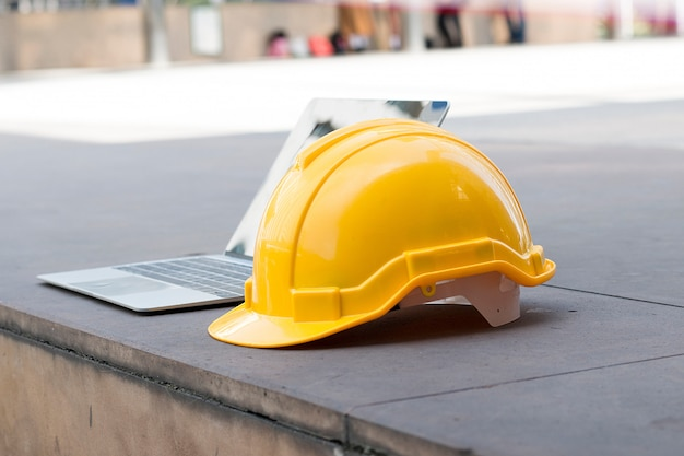 Chapéu de segurança e computador estão no canteiro de obras