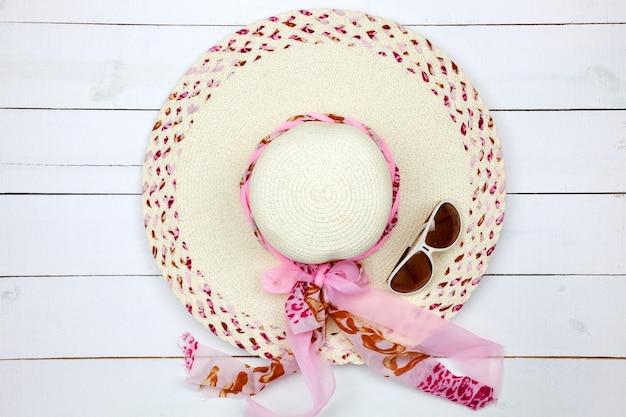 Chapéu de senhora bonita com óculos de sol em fundo branco de madeira.