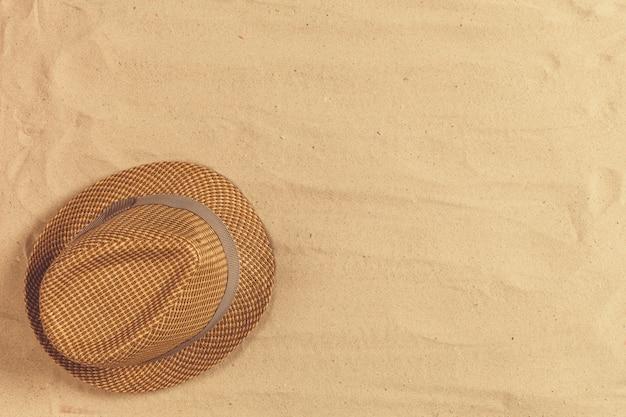 Chapéu de verão colocar na praia de areia tropical