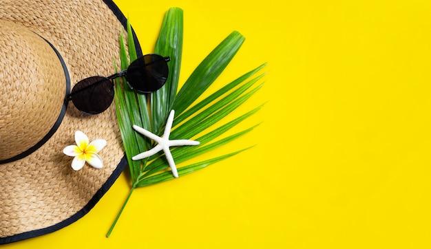 Chapéu de verão com óculos de sol em fundo amarelo. aproveite o conceito de férias.