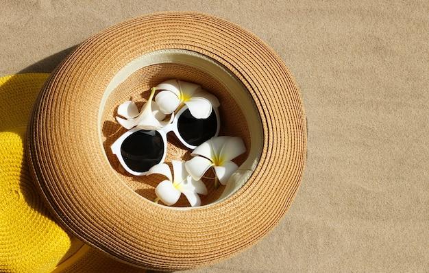 Chapéu de verão com óculos escuros e flores de plumeria na areia
