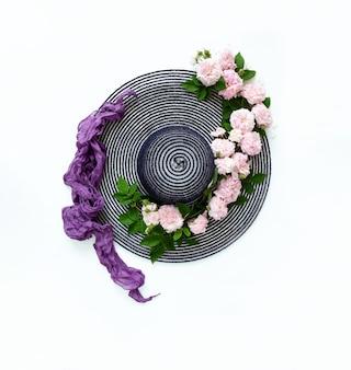 Chapéu de verão com um padrão de rosas frescas naturais e um lenço roxo de seda clara sobre fundo branco.
