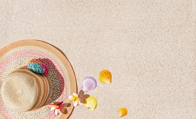 Chapéu de verão e conchas do mar na areia, vista superior, cópia espaço