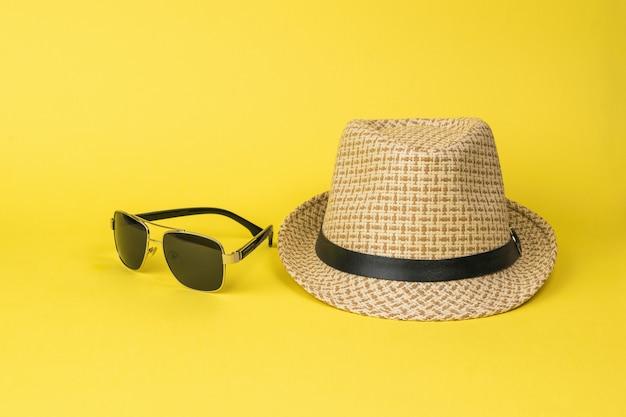 Chapéu de verão masculino e óculos escuros sobre um fundo amarelo. acessórios para homem.