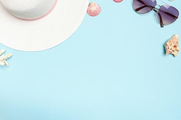 Chapéu de verão, óculos, conchas, corais em um fundo
