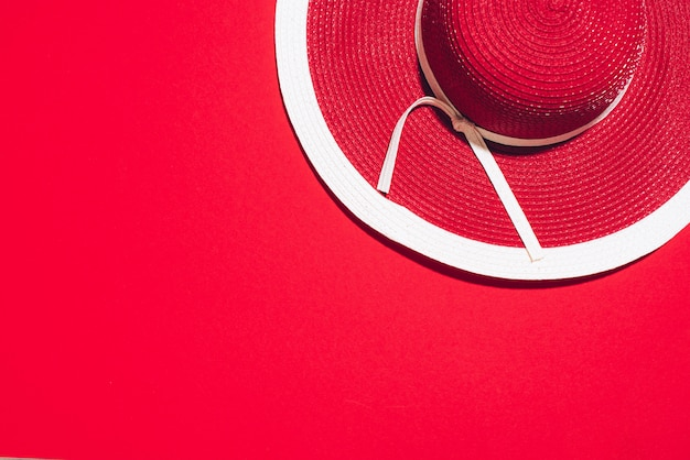 Chapéu de verão vermelho feminino em fundo de papel