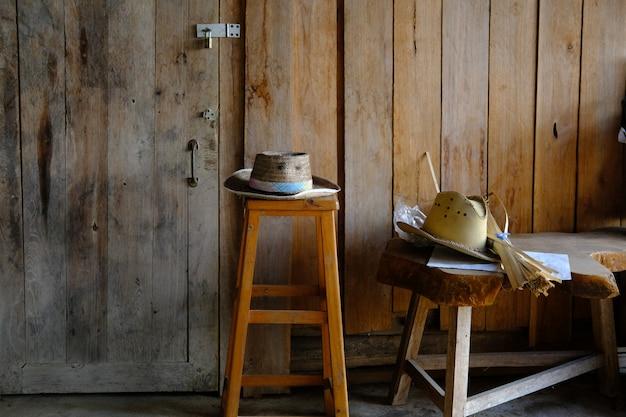 Chapéu de vime no banquinho de madeira na casa de campo rural
