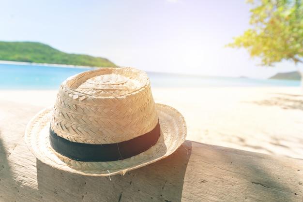 Chapéu de vintagestraw na madeira com o céu fresco da praia e do beira-mar.