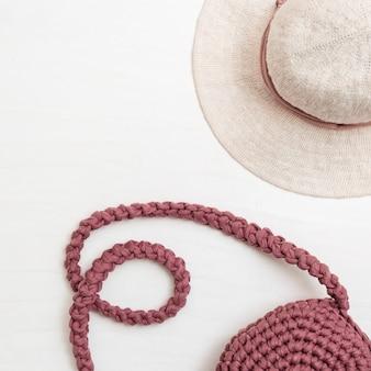Chapéu e bolsa obscuros da cor cor-de-rosa no fundo claro