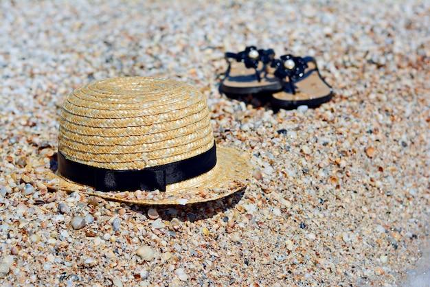 Chapéu e chinelos em uma praia de areia