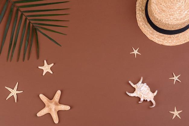 Chapéu e conchas e estrelas do mar em uma superfície colorida