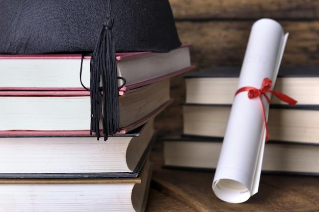 Chapéu e dilmoma com livros empilhados