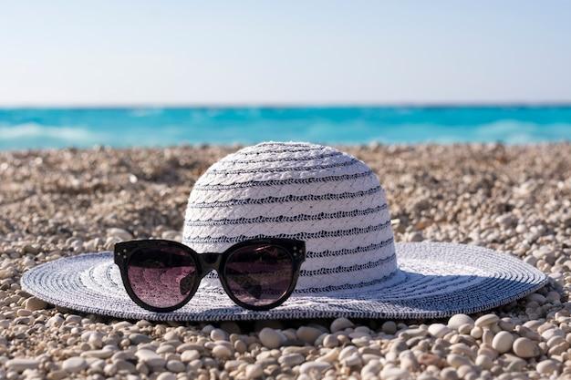 Chapéu e óculos de sol na praia. conceito de férias de verão.