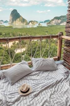 Chapéu e travesseiro na cama em uma varanda de madeira com vista para o mar e as montanhas