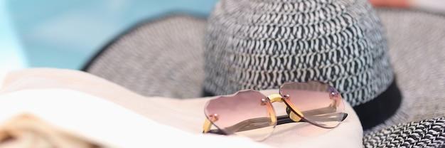 Chapéu elegante com óculos de sol deitado na espreguiçadeira