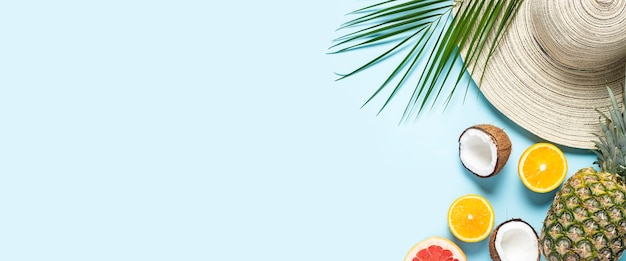 Chapéu feminino com aba larga, frutas tropicais e um galho de palmeira sobre um fundo azul.