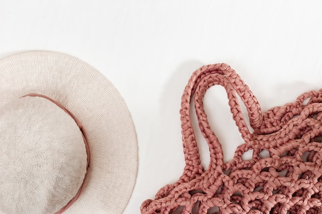 Chapéu feminino com abas largas e bolsa de praia de malha de cor rosa. vista do topo.
