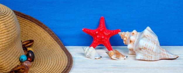 Chapéu feminino, conchas e estrelas do mar na mesa de madeira. conceito de verão