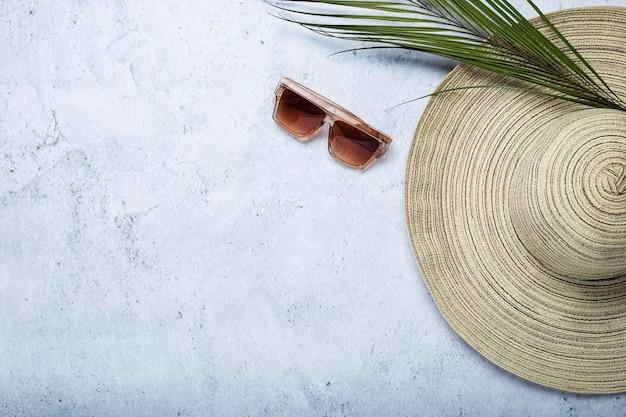 Chapéu feminino, óculos escuros e uma folha de uma palmeira em um fundo de concreto. vista superior, configuração plana.