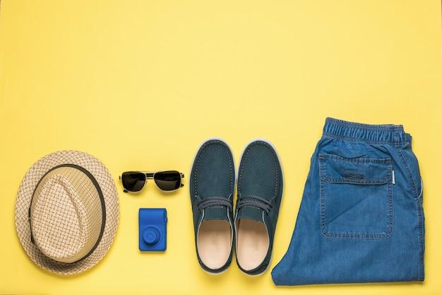 Chapéu, jeans, sapatos, câmera e óculos em um fundo amarelo. espaço para o texto. postura plana.