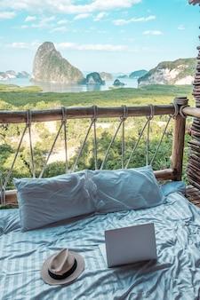 Chapéu, laptop e travesseiro em uma cama em uma varanda de madeira com vista para o mar e as montanhas